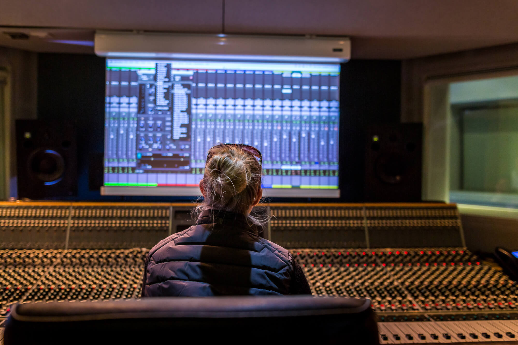 A student behind the mixing desk in the music studio