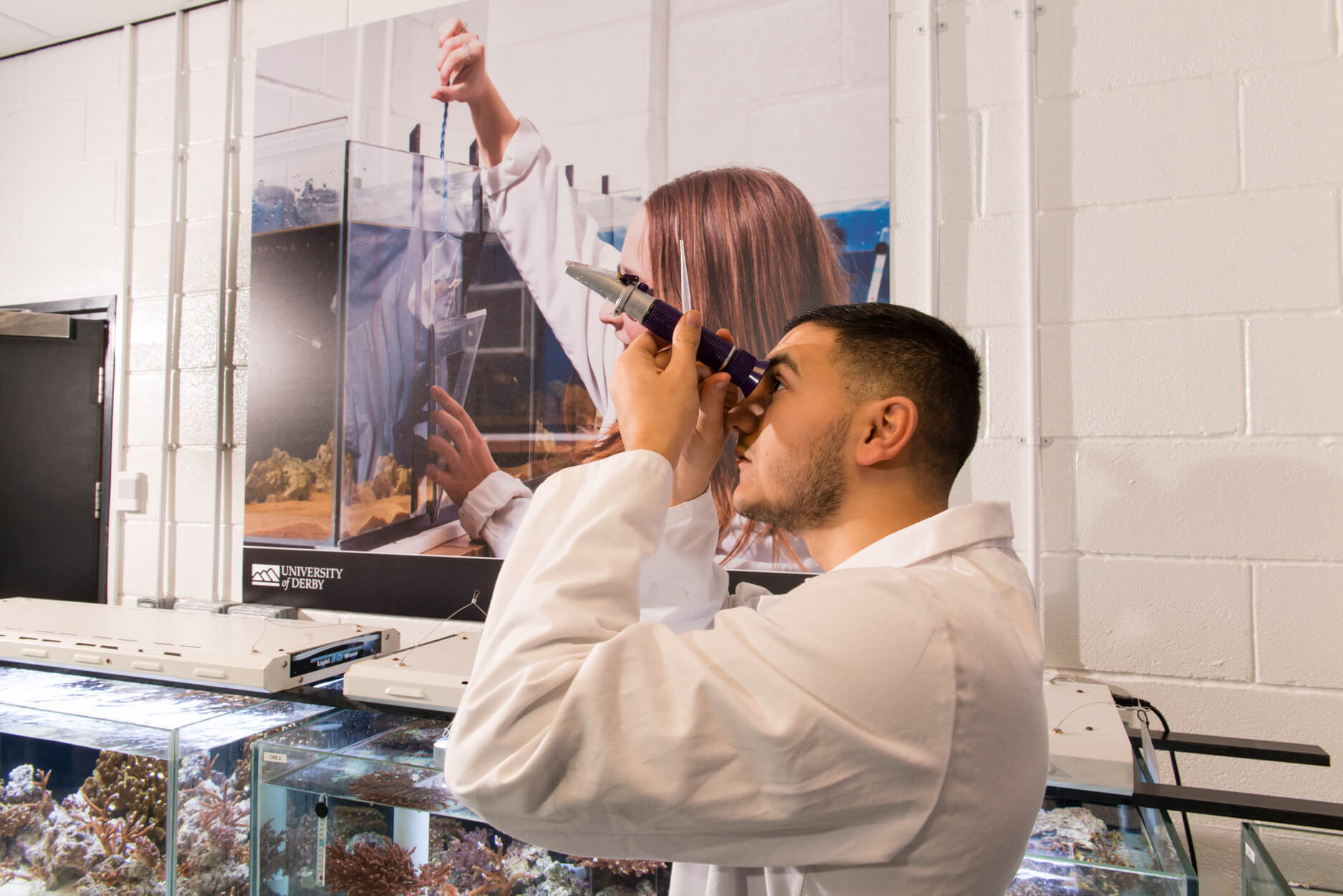 Students in the Aquatic Research Facility using a microscope device