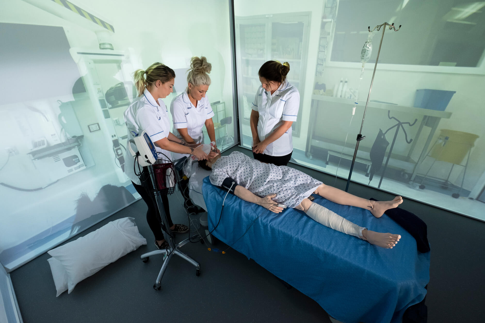 Students examining a patient in the immersive suite