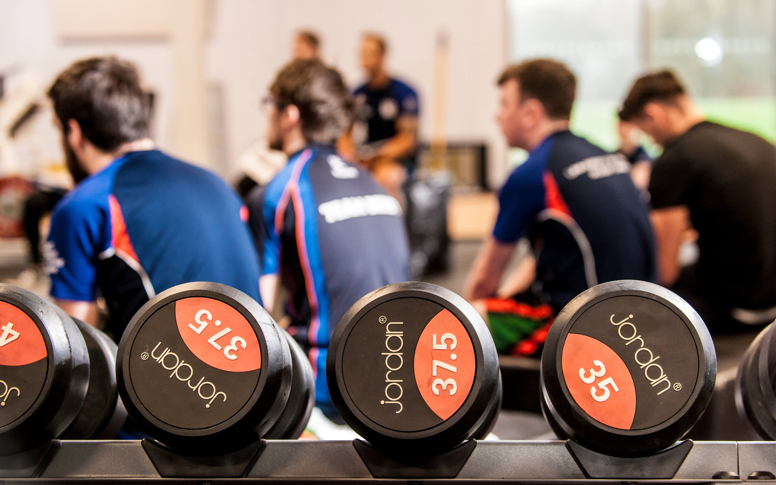Image of dumbbells with students learning in the Strength and Conditioning Suite