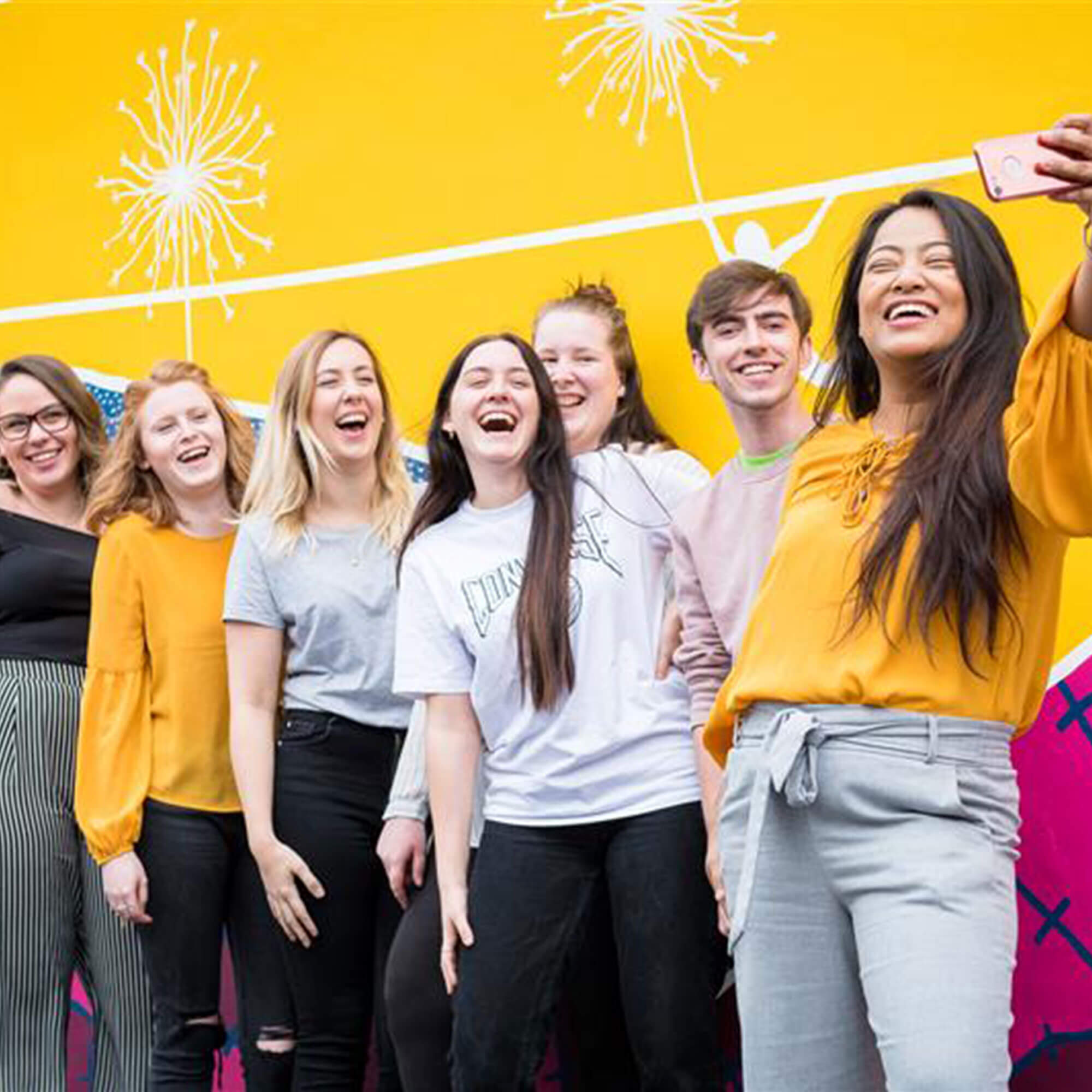 Group of students by a yellow wall taking a selfie