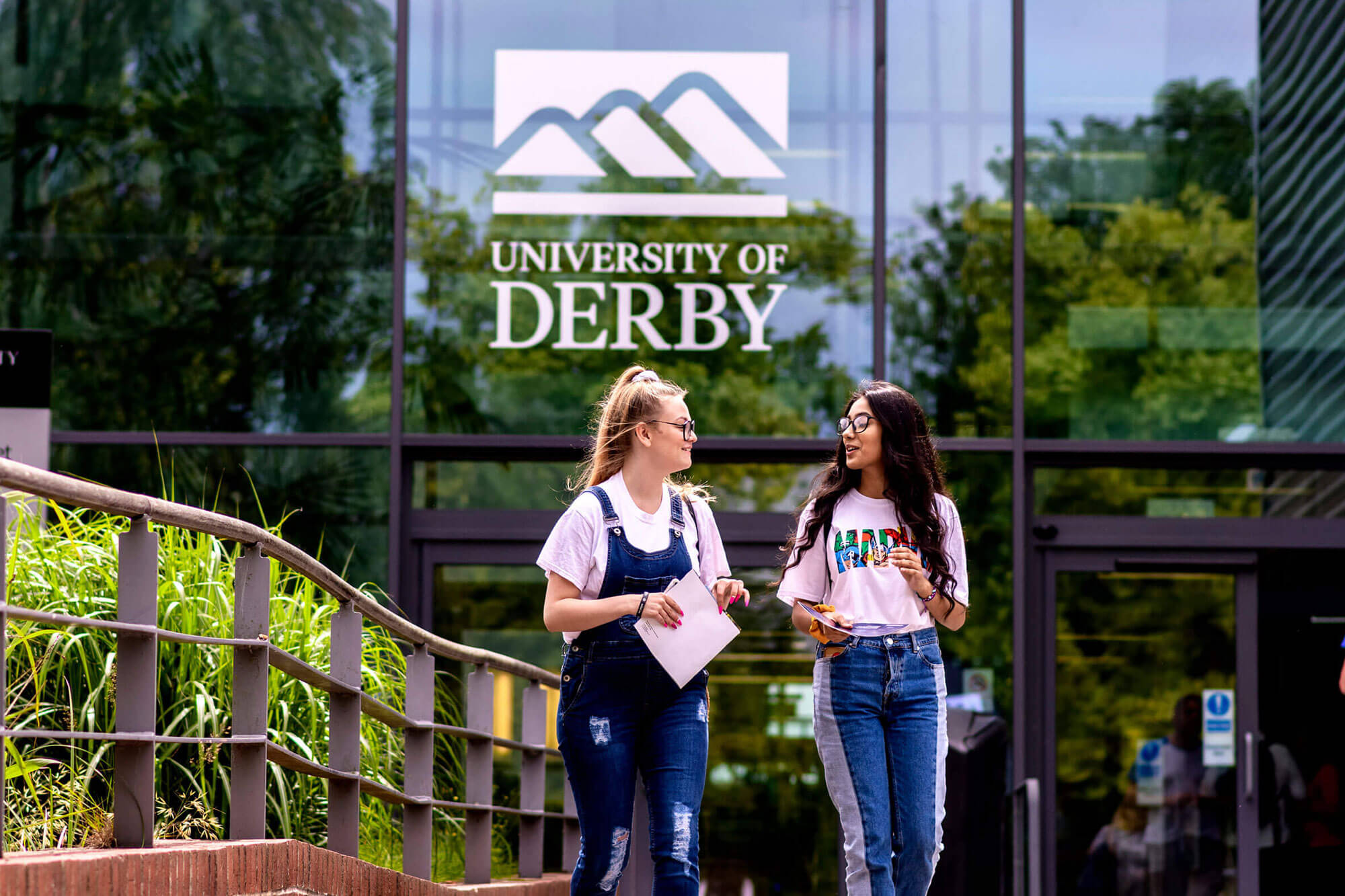 Two students walking outside the University of Derby campus Markeaton Street site