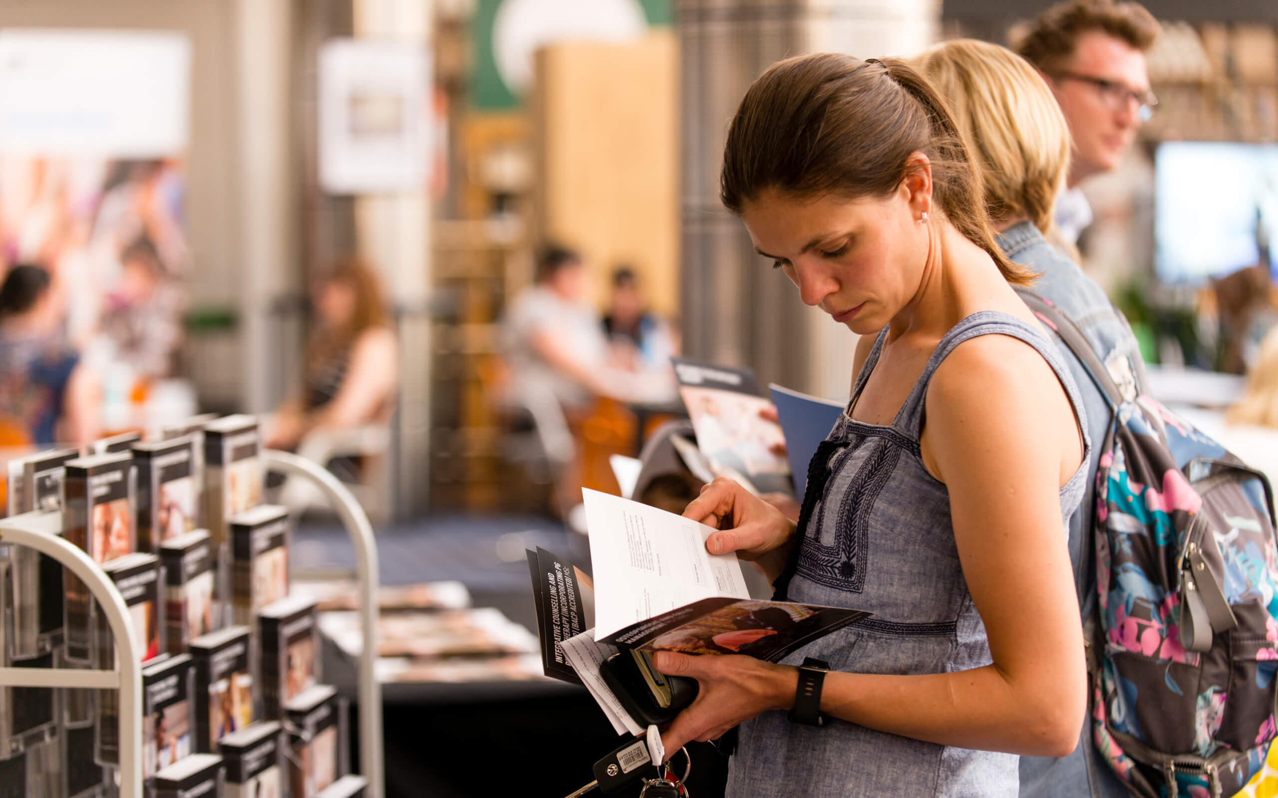 Woman looking through leaflet at Postgraduate Open Evening