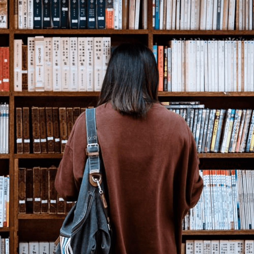 A student standing by bookshelves