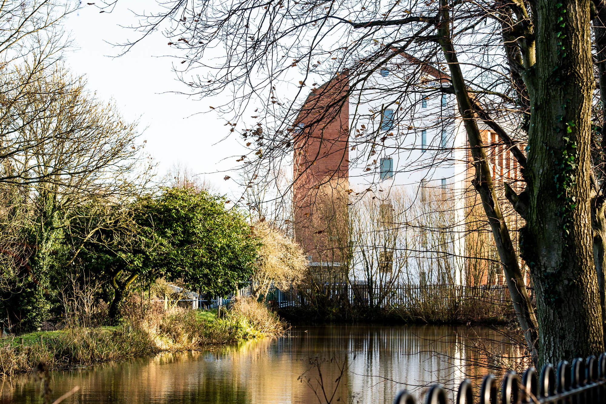 Britannia Mill surrounded by greenery and a river