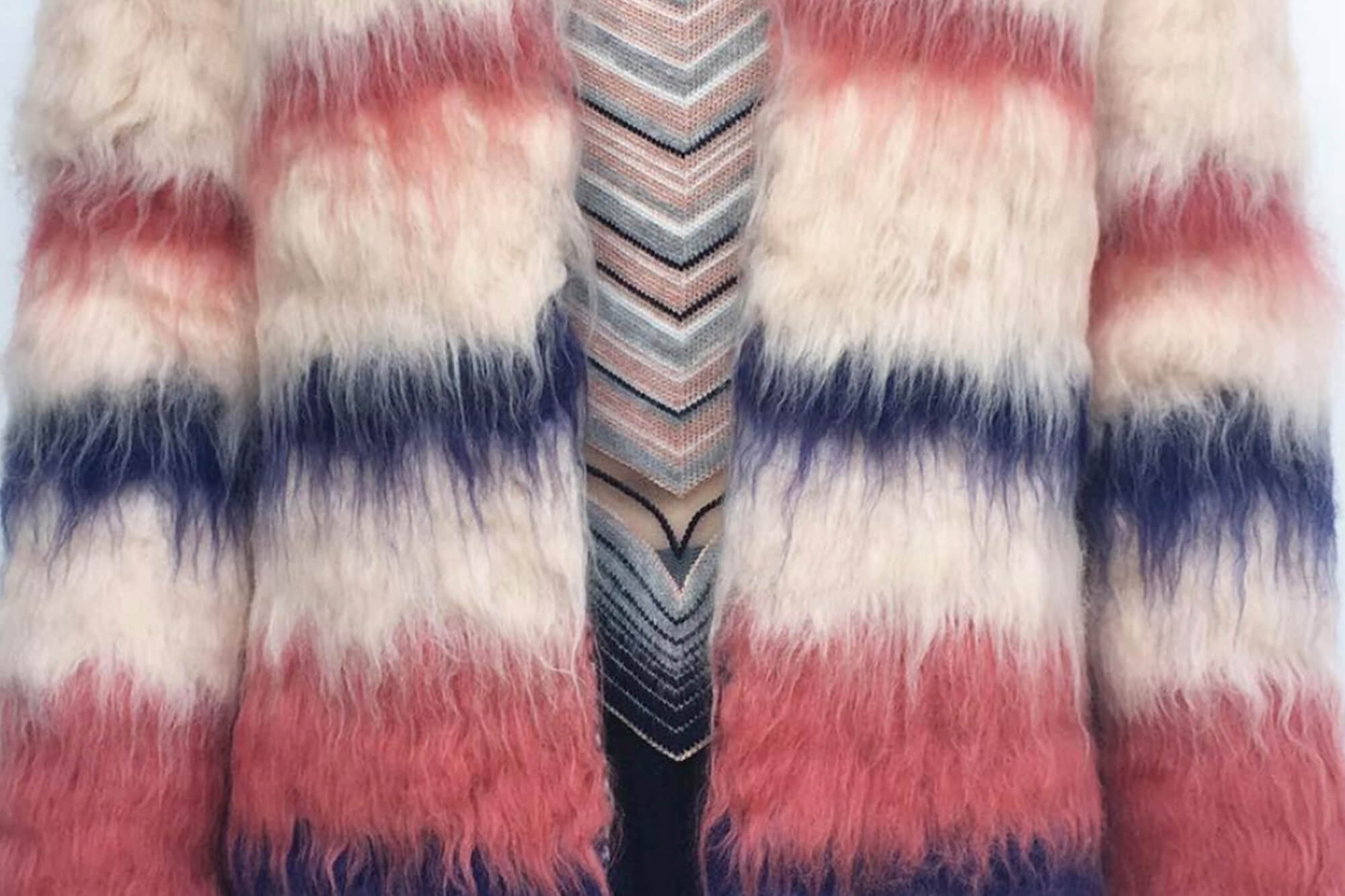 A pink, blue and white fluffy garment over a pastel knitted top