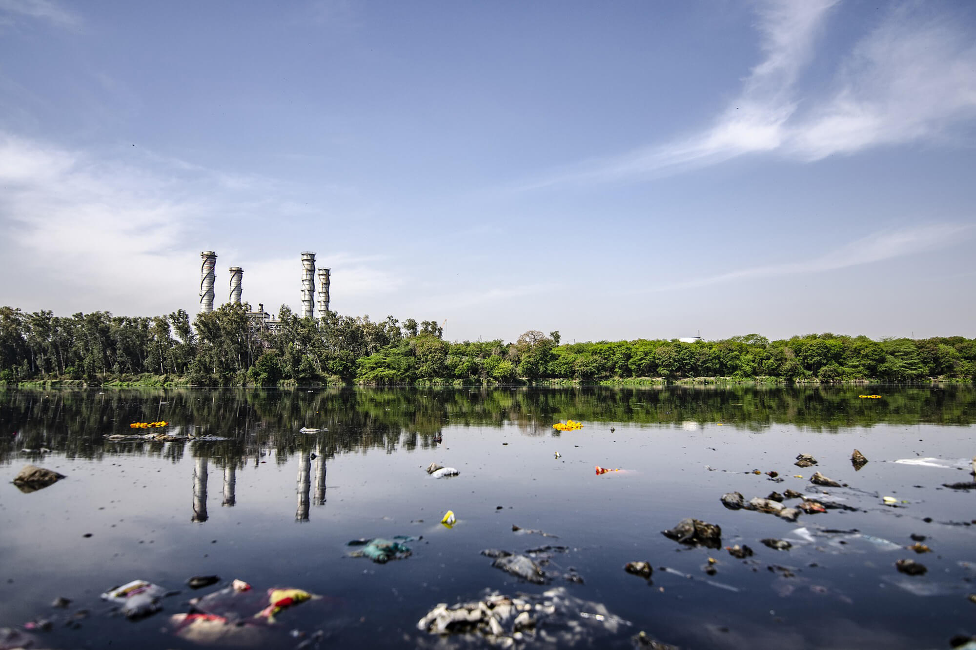 polluted water with rubbish and a factory in the background across the river