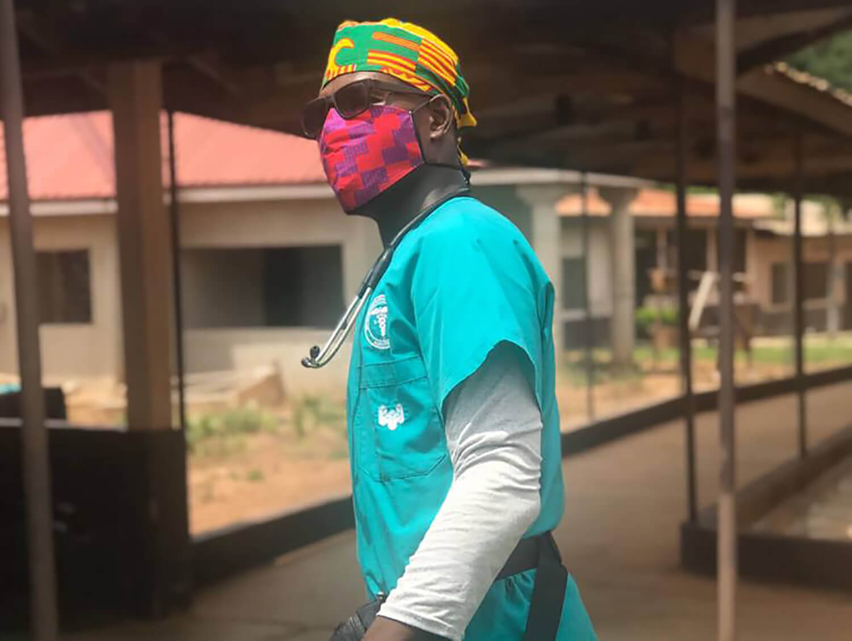 Daniel Nang-Tege Ekumah in nursing scrubs, a hat and mask