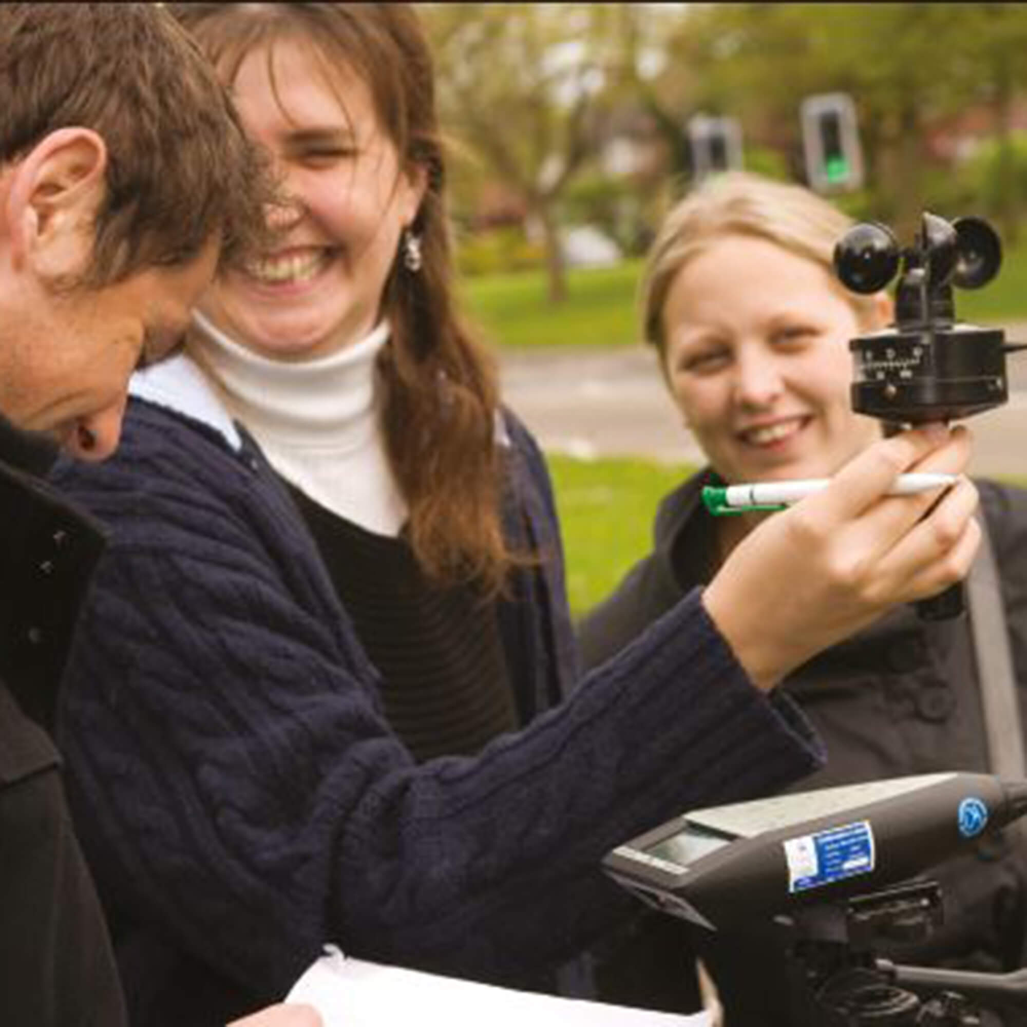 Three students using noise measuring equipment outdoors