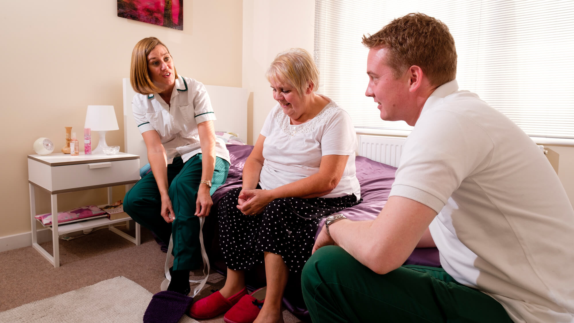 Students help patient in their home on a bed