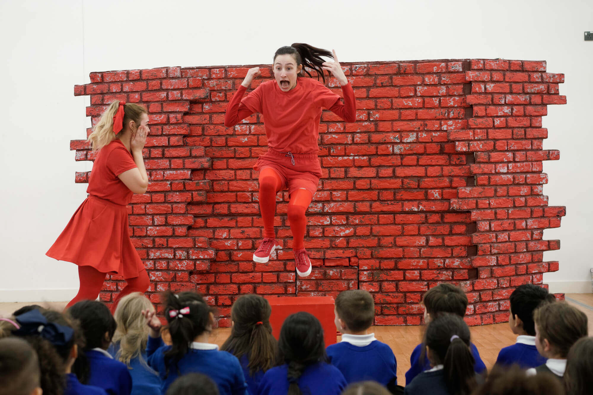 A woman in a red tracksuit jumps in front of a stage set of a brick wall