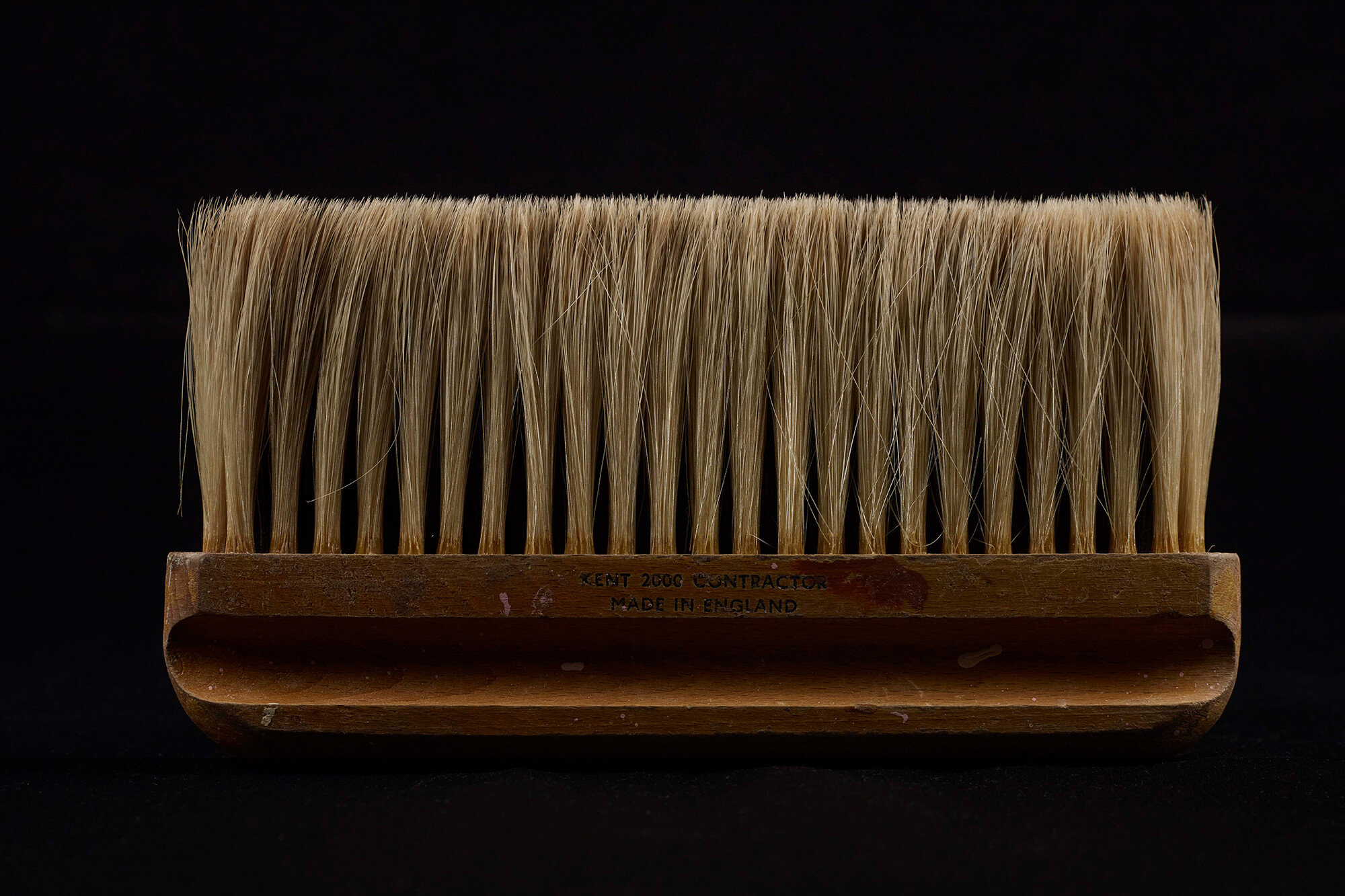 Close up image of a bristle brush on a black background
