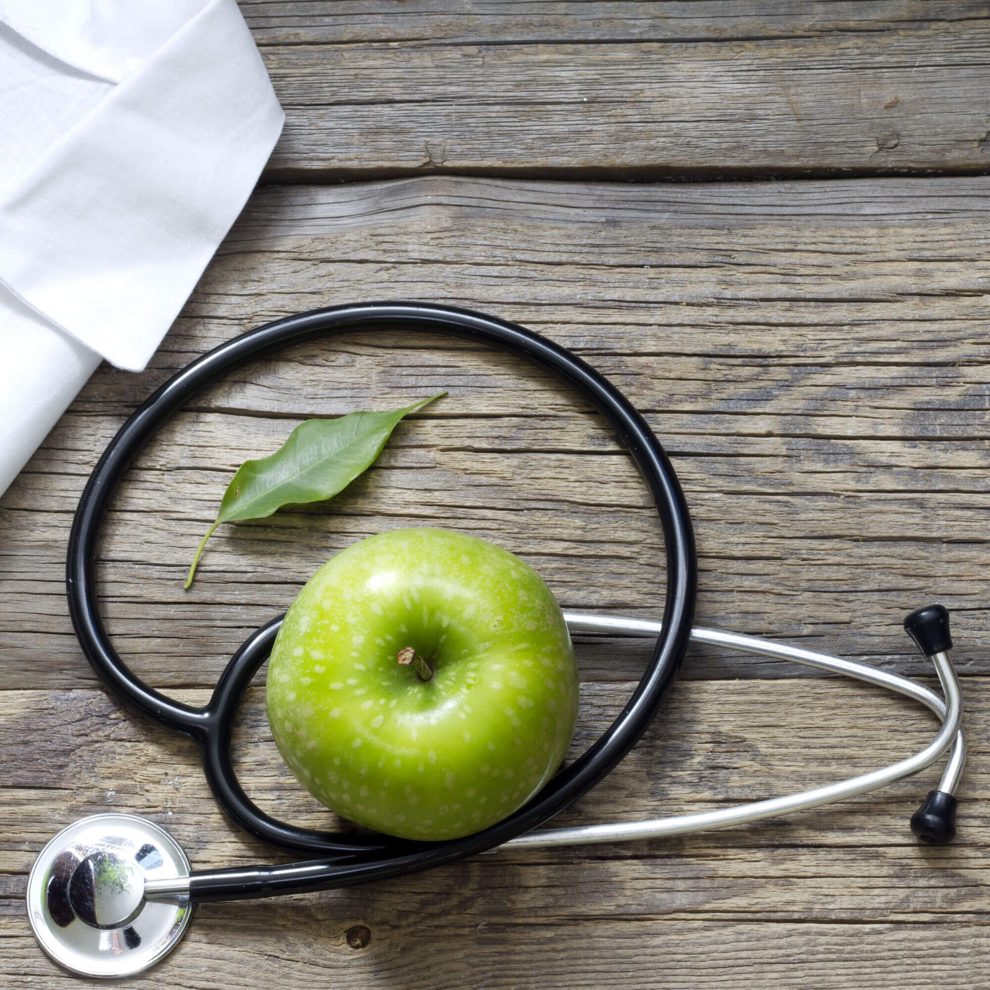 Green apple on a table with a stethoscope