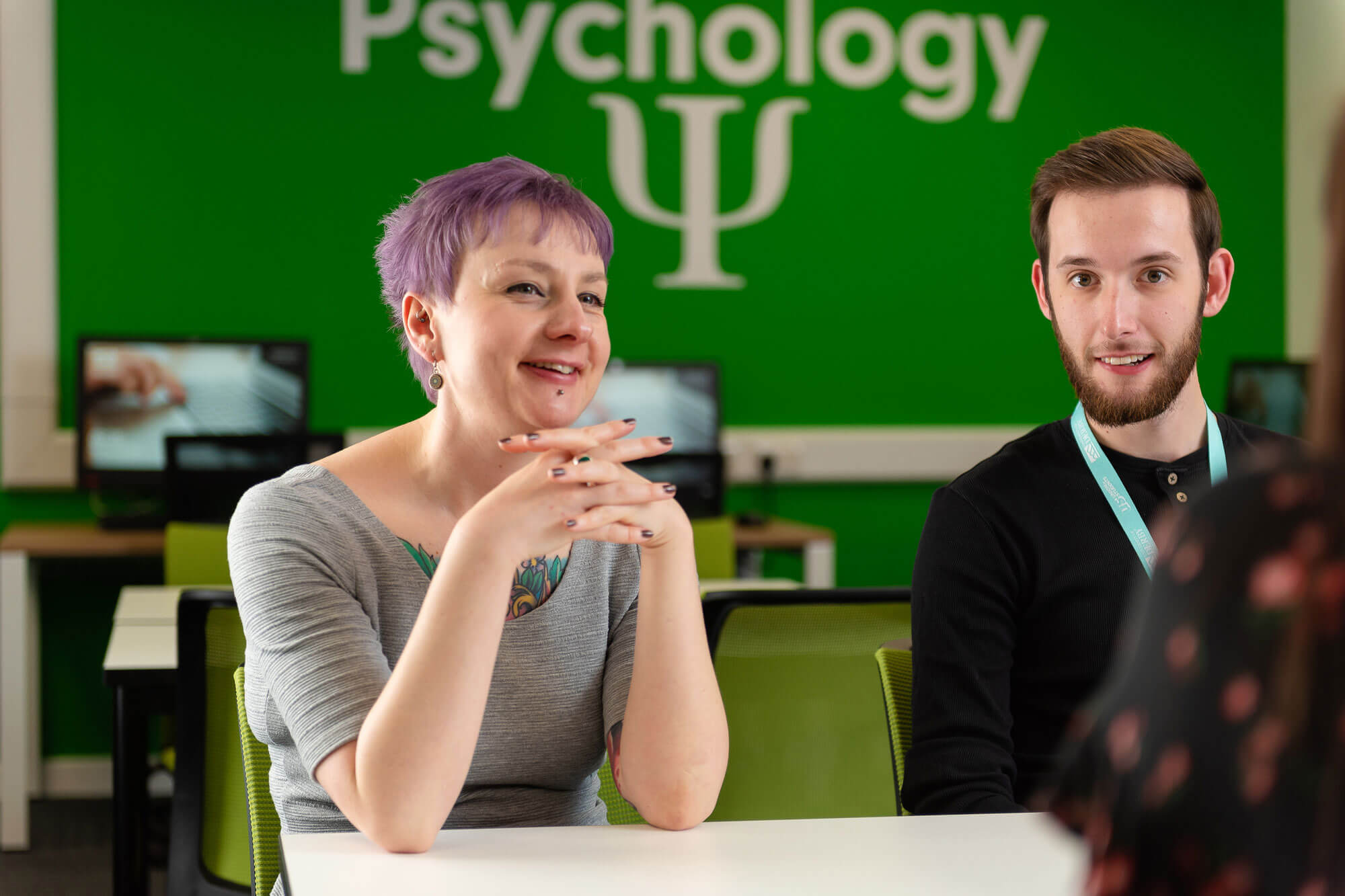 Lady and gentleman set at a desk with a Psychology backdrop poster