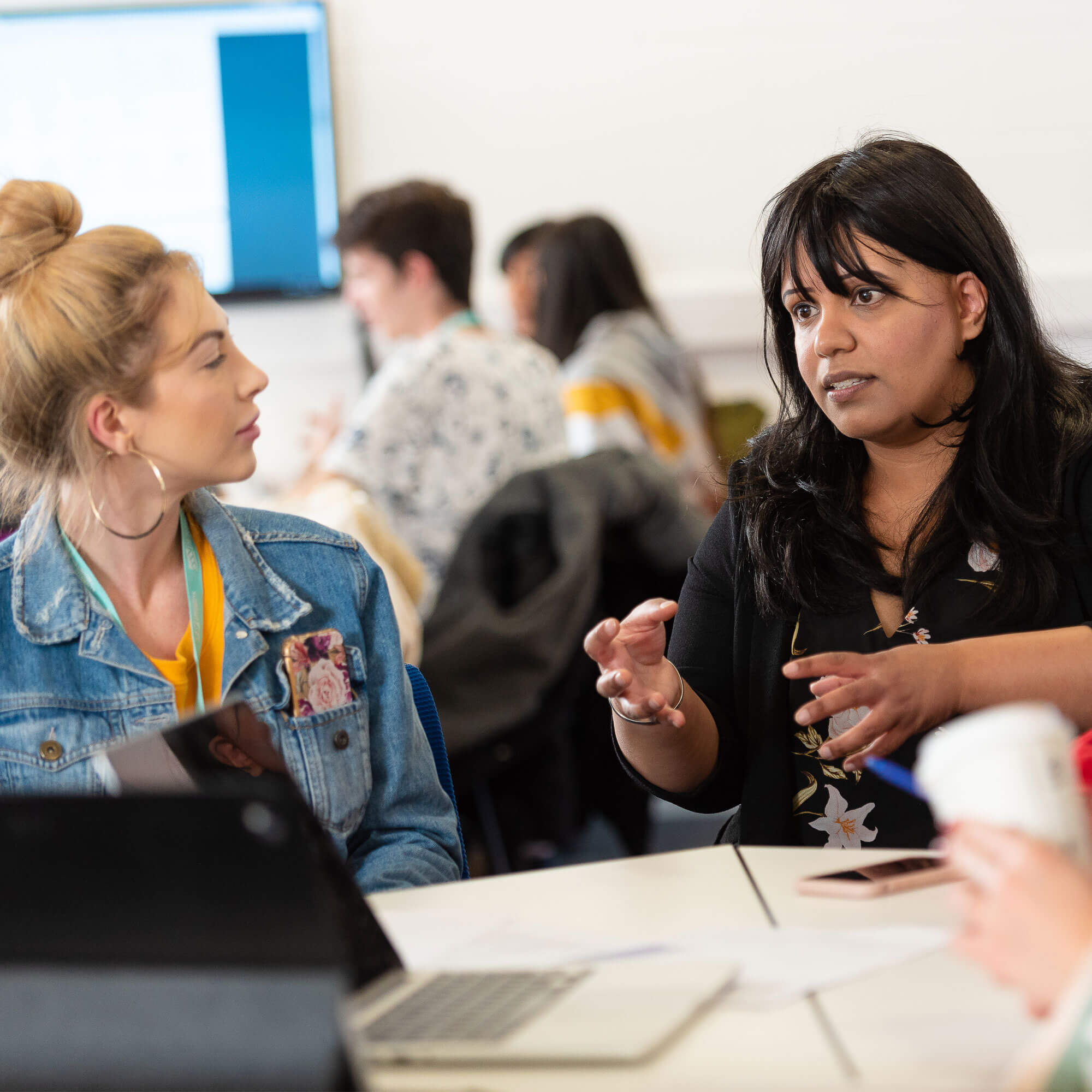 A female academic talking to a female workshop attendee