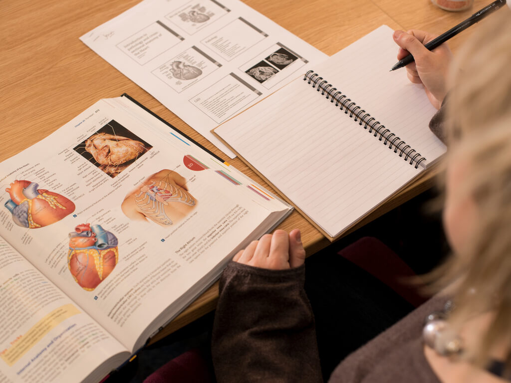 Student reading a radiography textbook in class