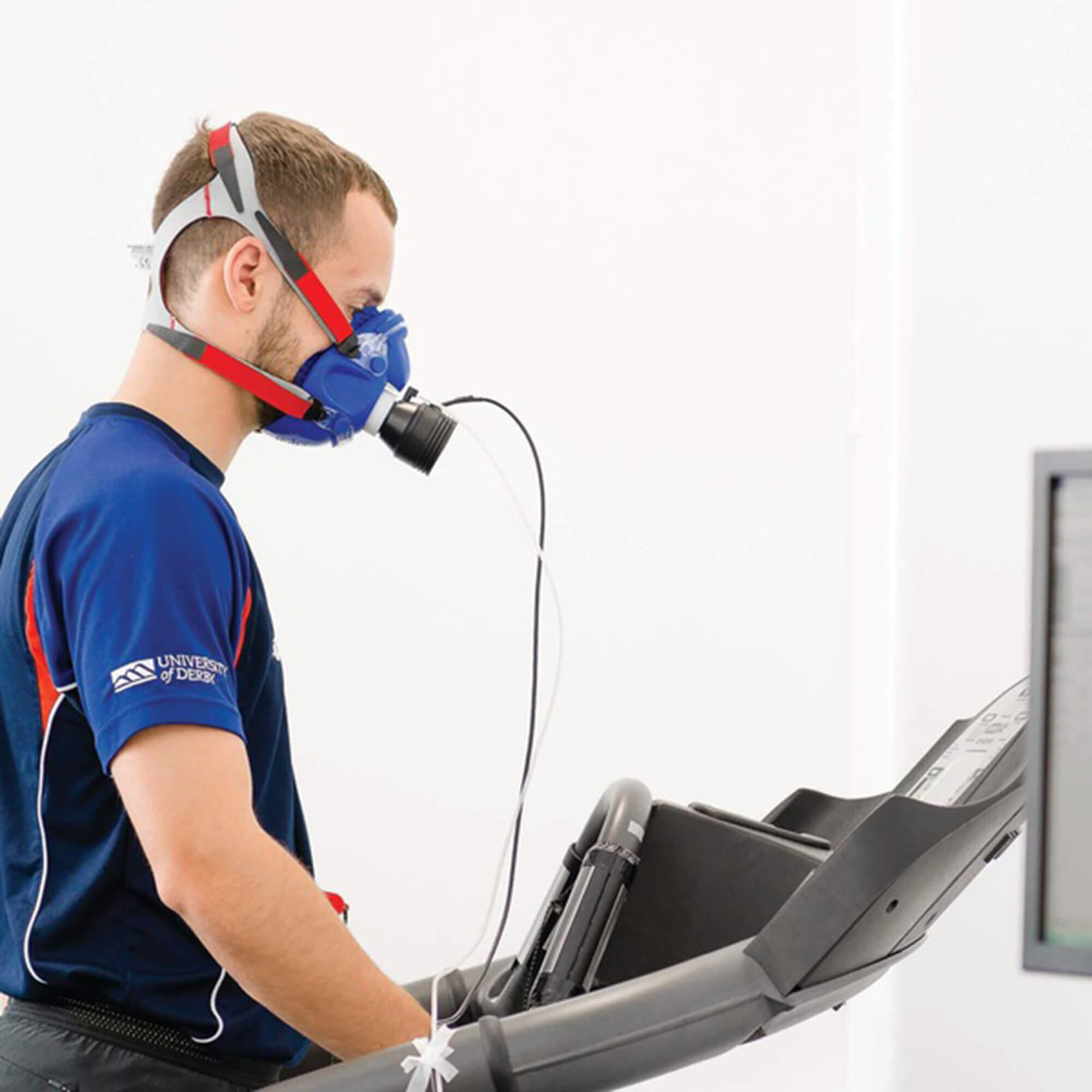 A male student walking on a treadmill with a breathing monitor on