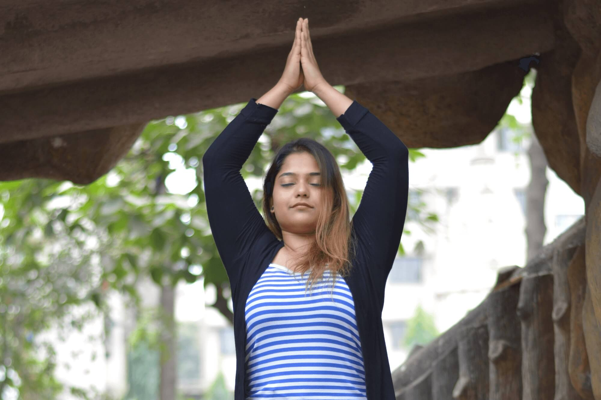 Aishwarya Deshpande stands with her palms closed and her arms in a triangle shape above her head with her eyes closed