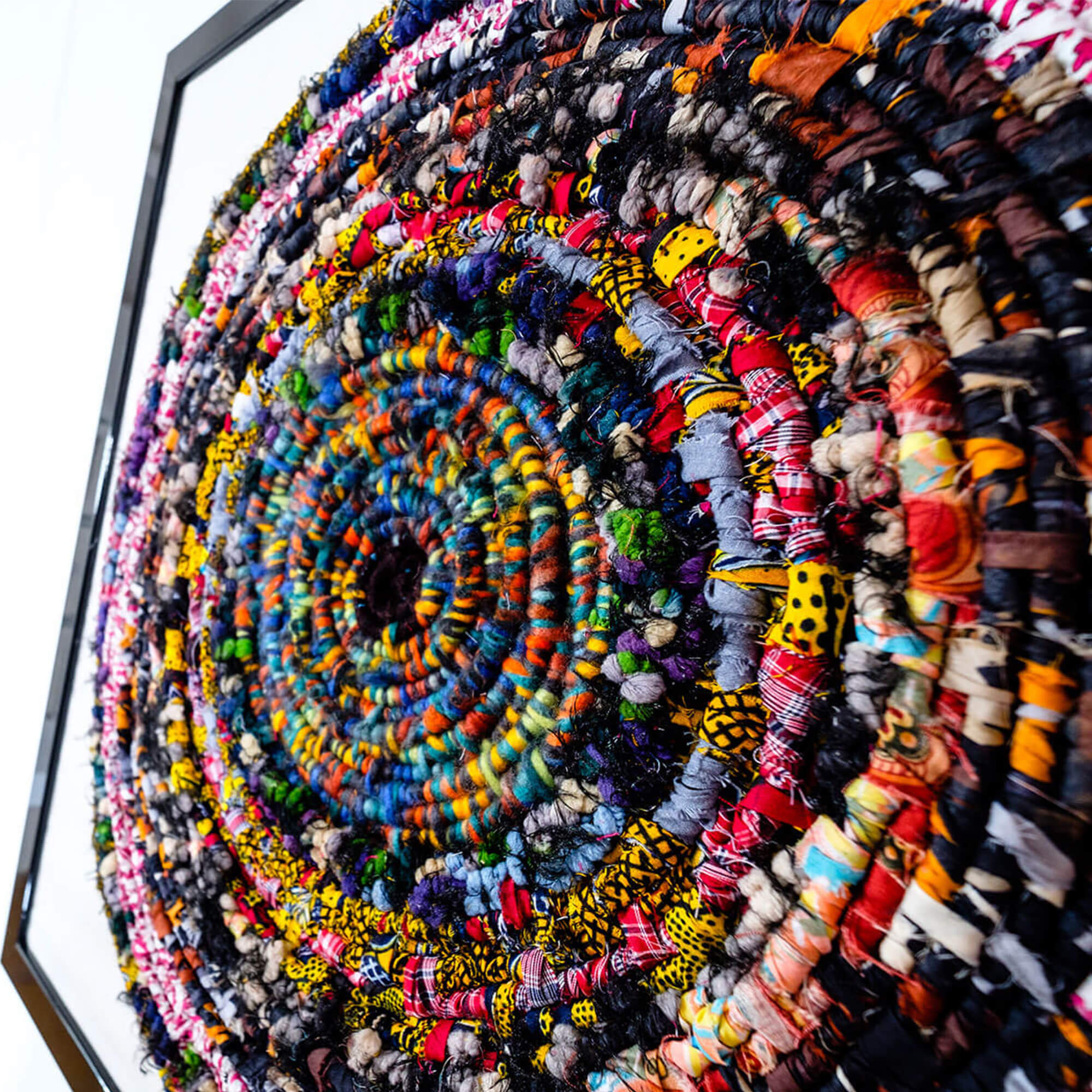 Close up of brightly coloured fabrics twisted together to make a spiral