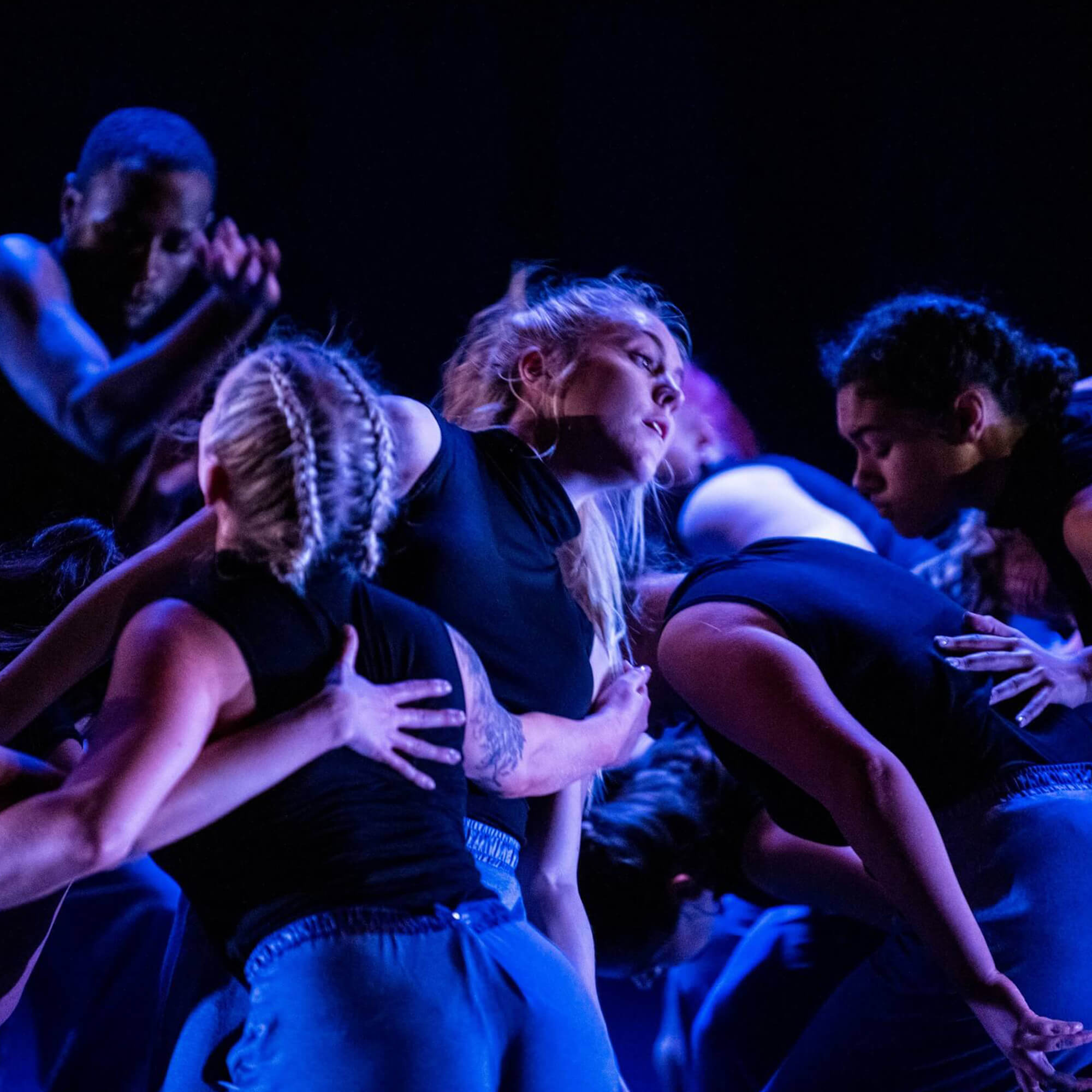Group of dancers huddle closely in a dark theatre environment