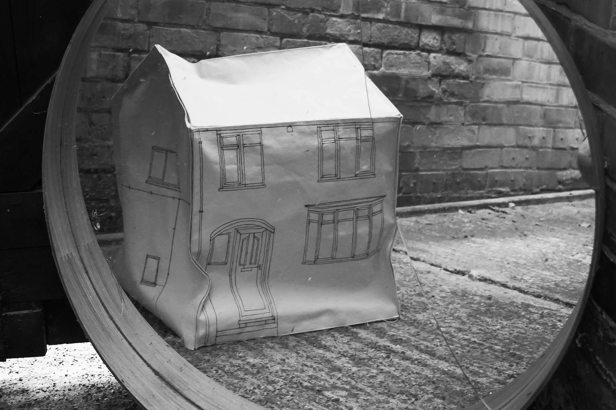 Black and white image of a paper model of a house in front of a circular mirror in a brick environment