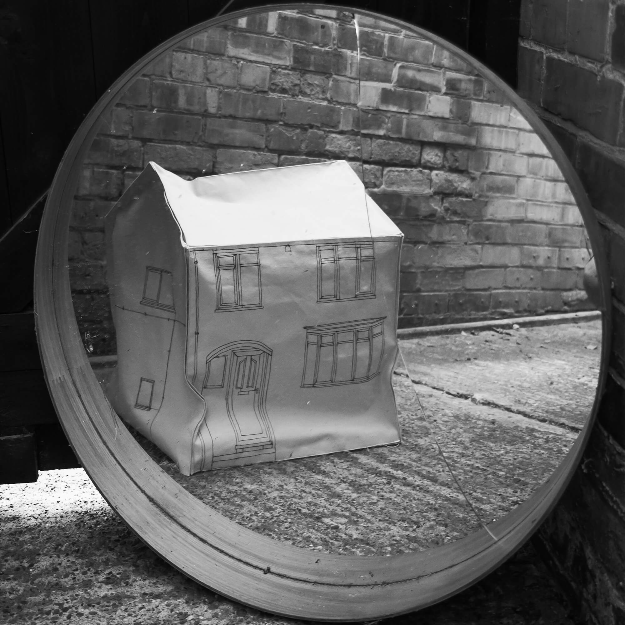 A black and white image of a paper model of a house shown in a mirror in a brick background