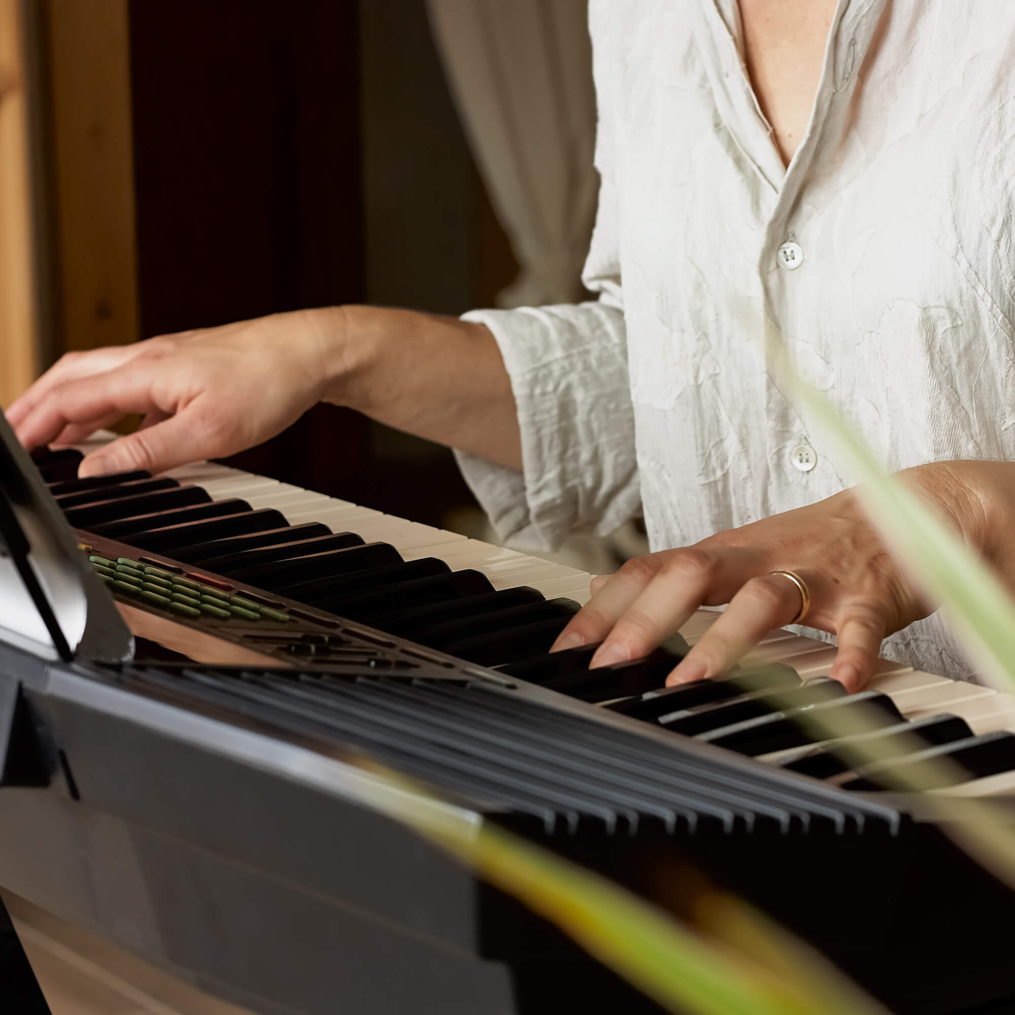 A person wearing a loose fitting white linen look shirt lays their hands on a keyboard next to a plant