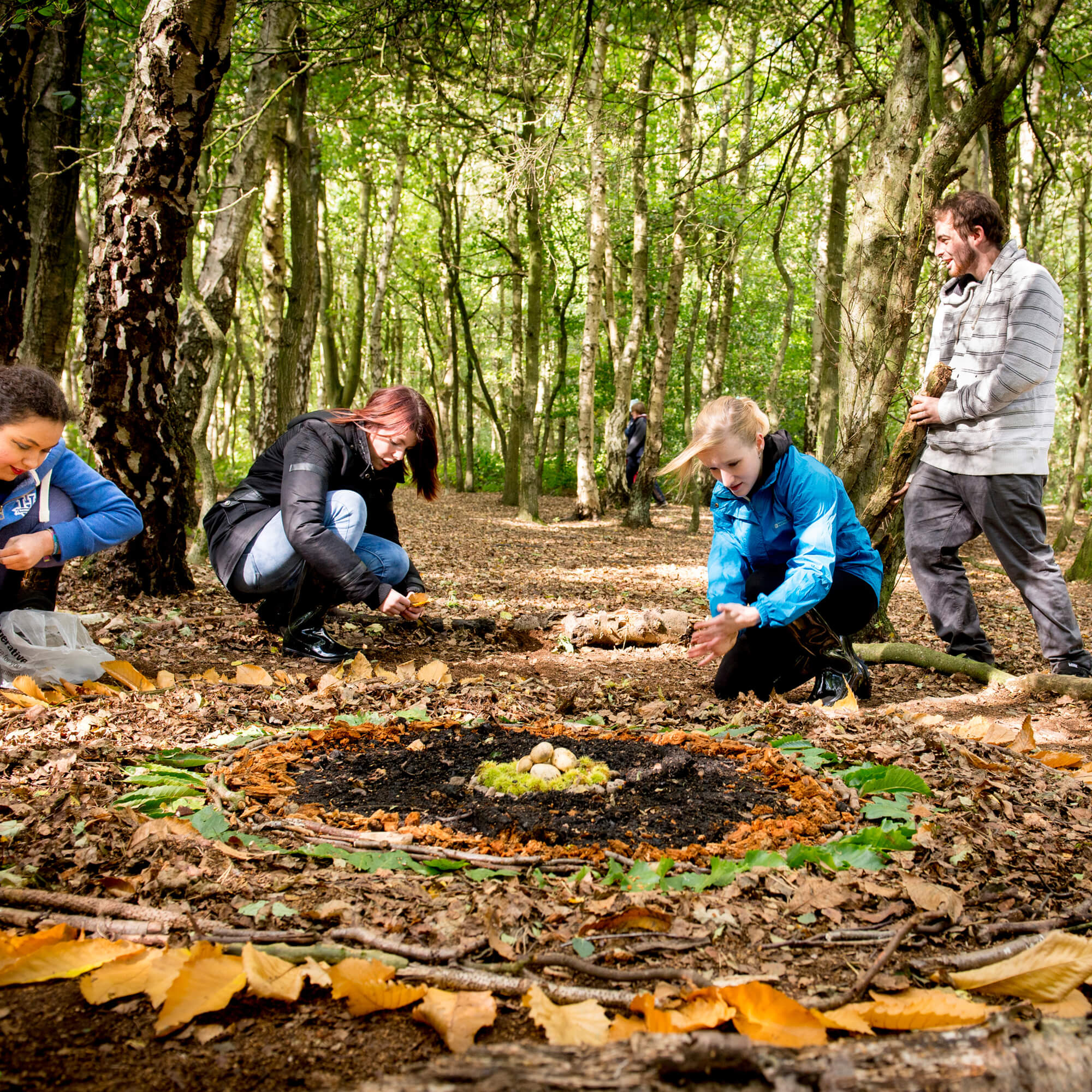 A group of people in outdoor clothing position leaves, sticks and stones in circular patterns in the woods