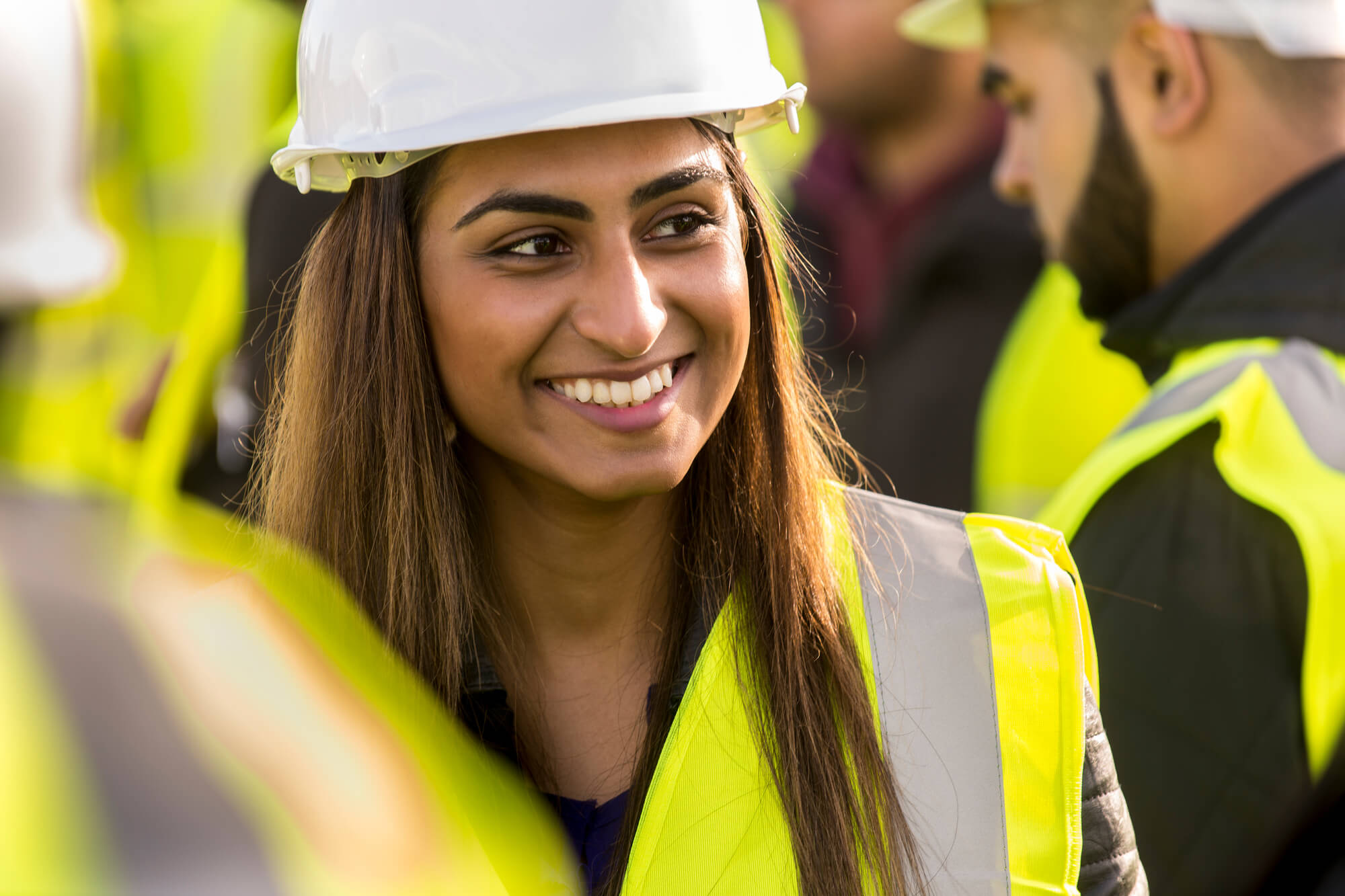 Construction and Civil Engineering student wearing hi-vis jacket and hard hat on a visit to a Radleigh Homes housing site