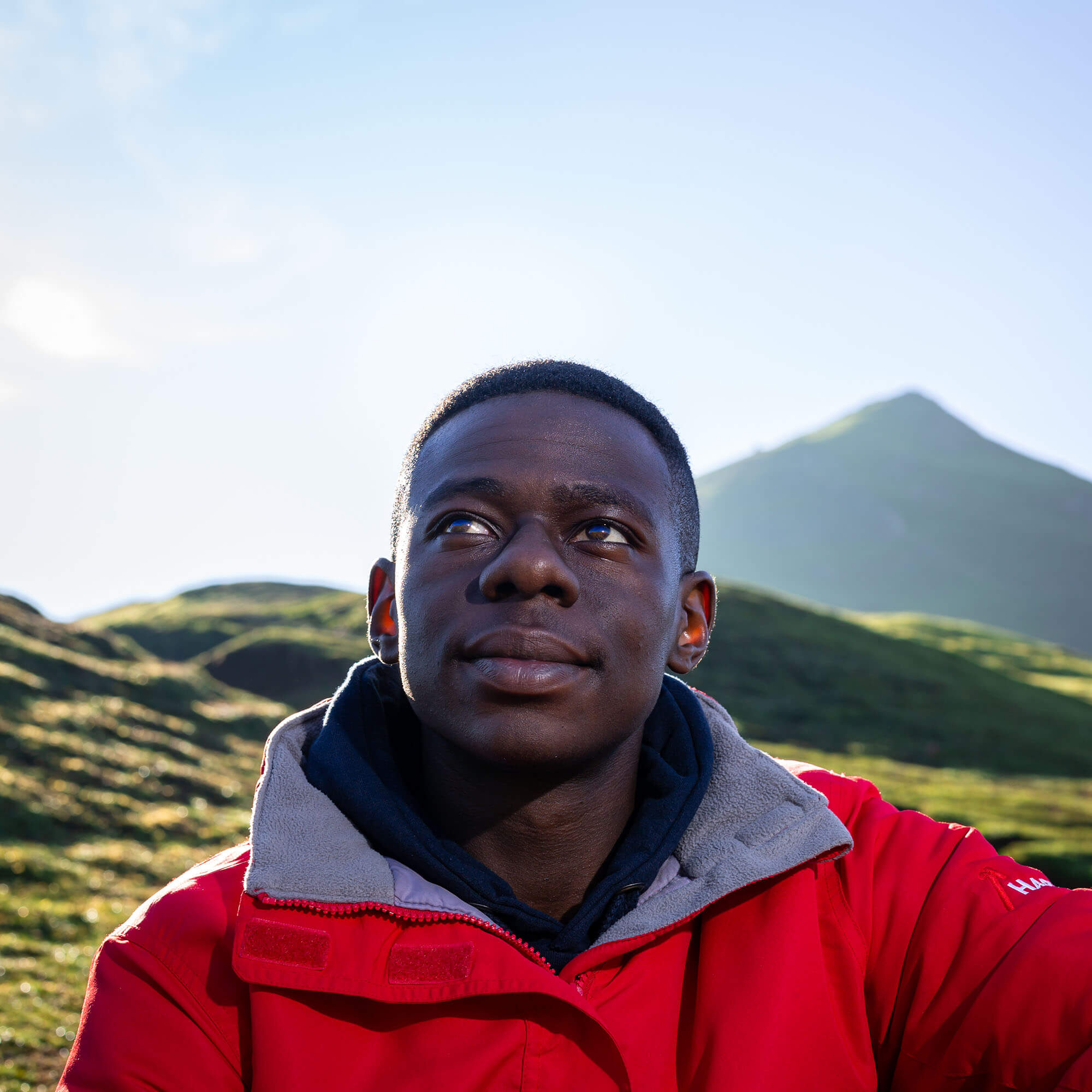 A University of Derby male student sits in the outdoors, wearing a red outdoor jacket, he looks up towards the blue sky with green grass and mountains behind him
