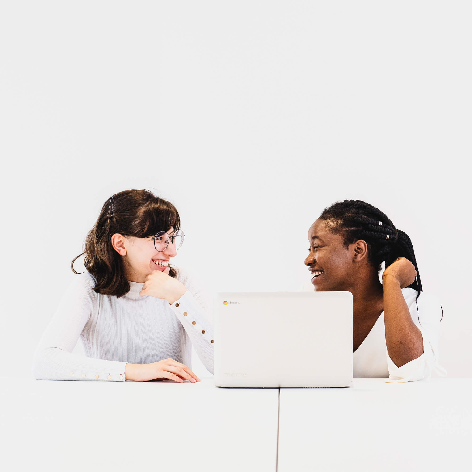 Image of two girls in front of a laptop chatting