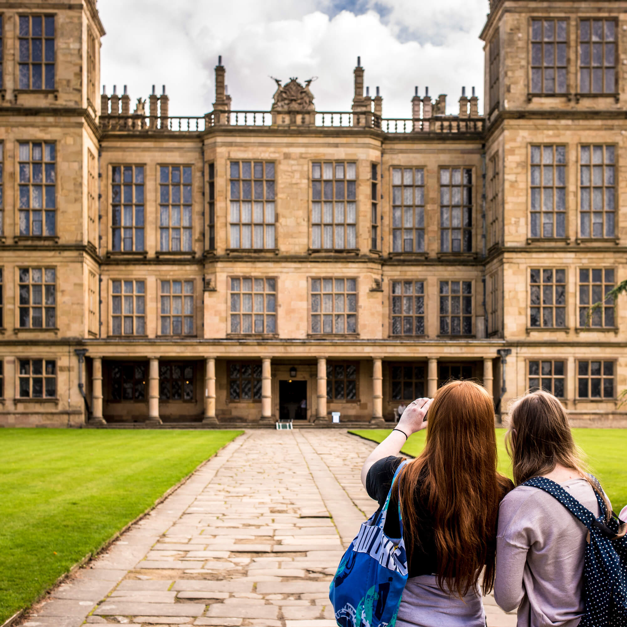 two students standing infront of a grand hall and taking pictures.