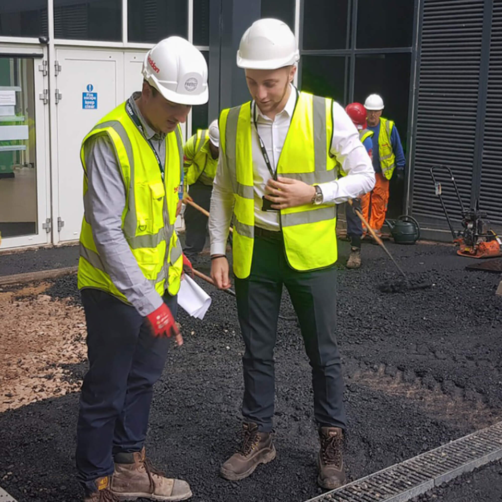 Male student working on site and being advised by another male employer