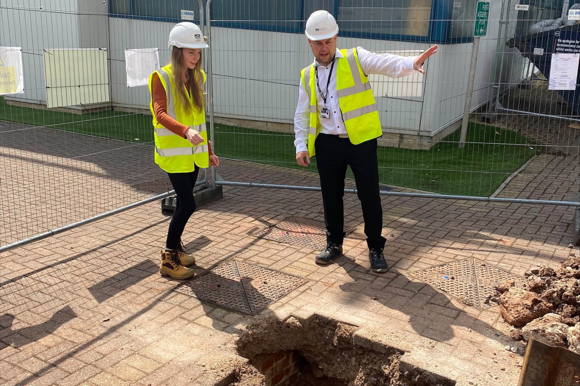 Female student and male estate team member analyse a hole in the ground