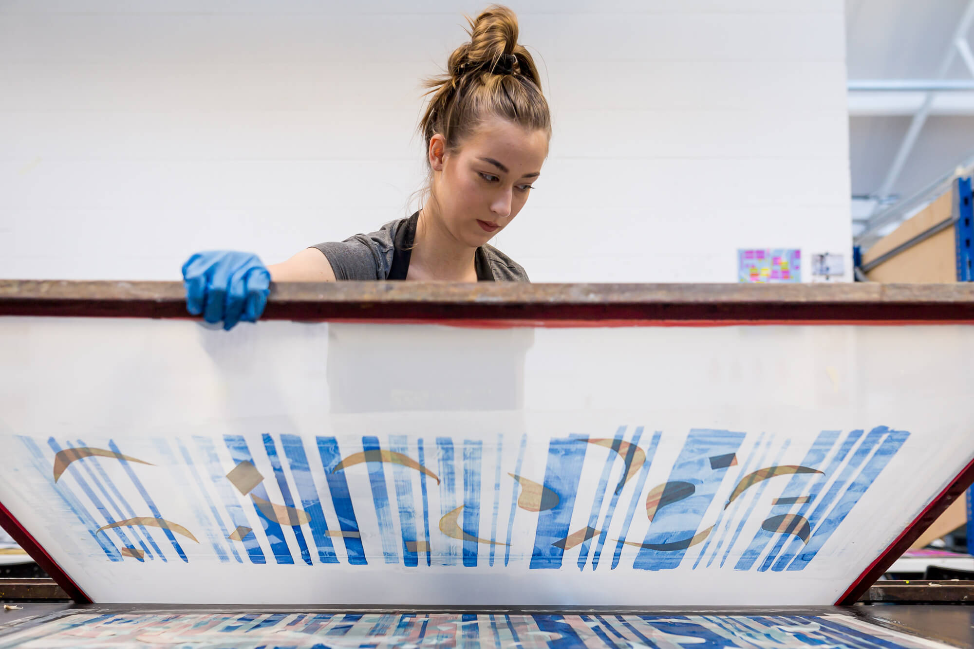 A female screenprints a picture with blue vertical lines and abstract shapes
