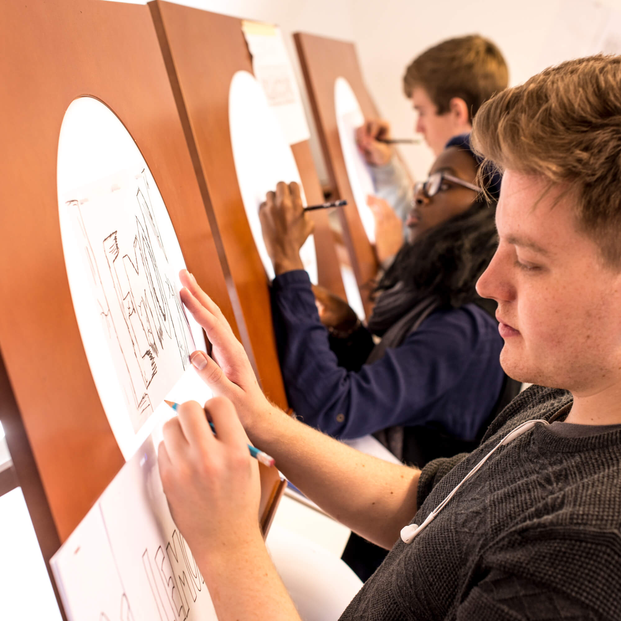A group of students work on their drawings on lightboxes