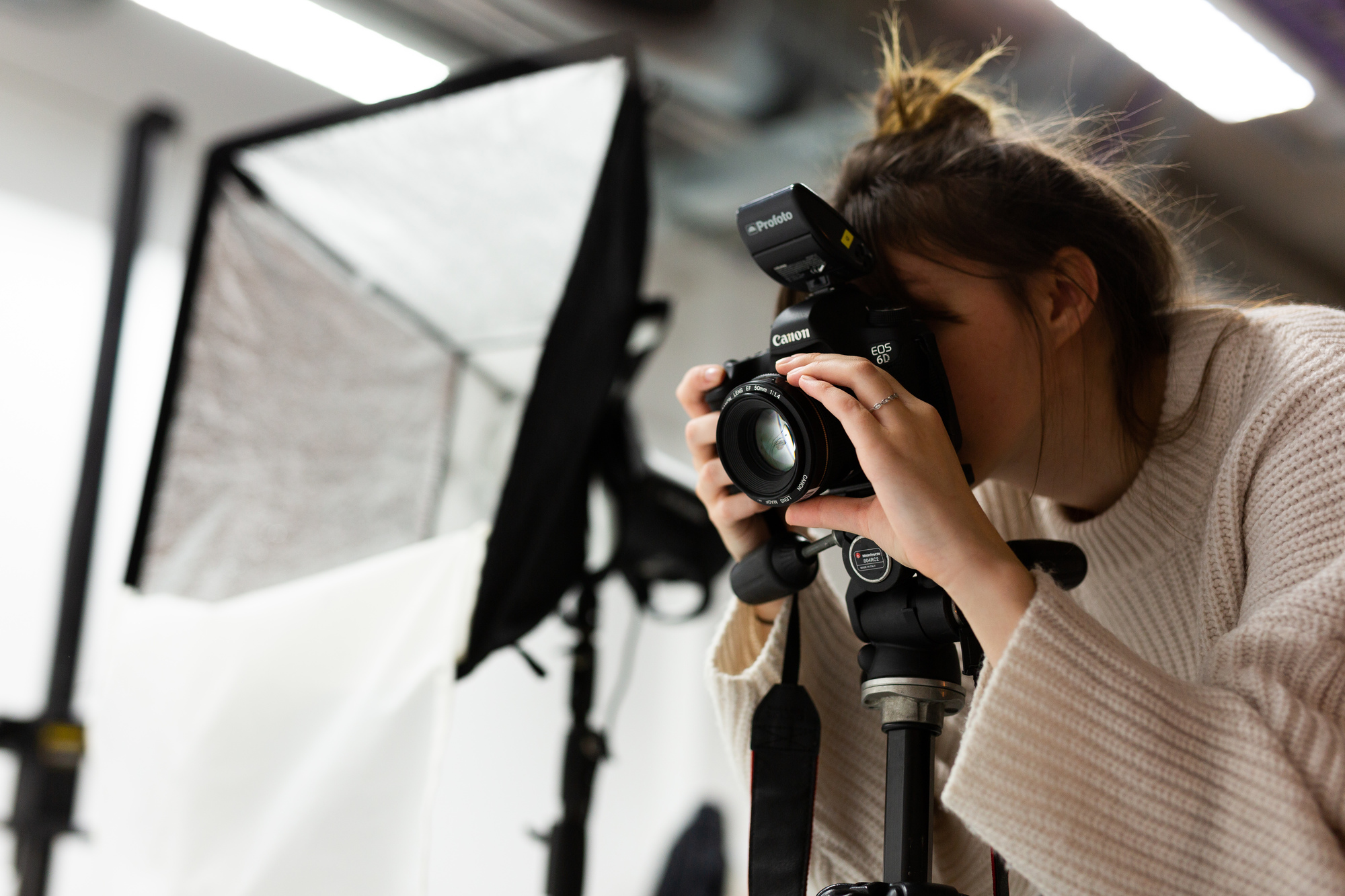 Female student looks through a camera with a specialist light in the background