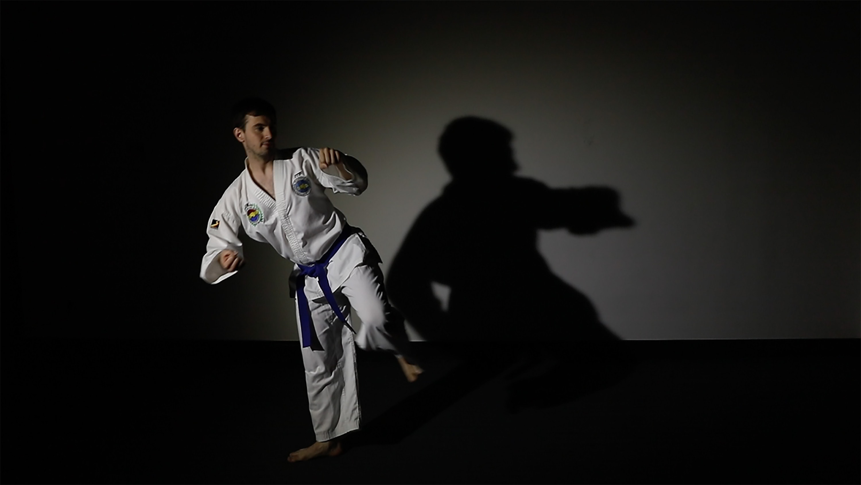 Martial arts motion of a man in a standing position lifting their left leg
