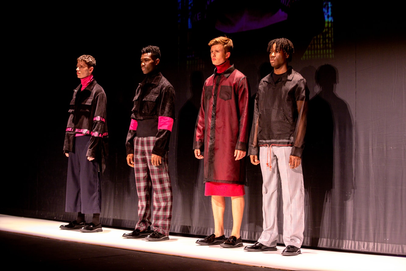 A lineup of male models in black and red clothes