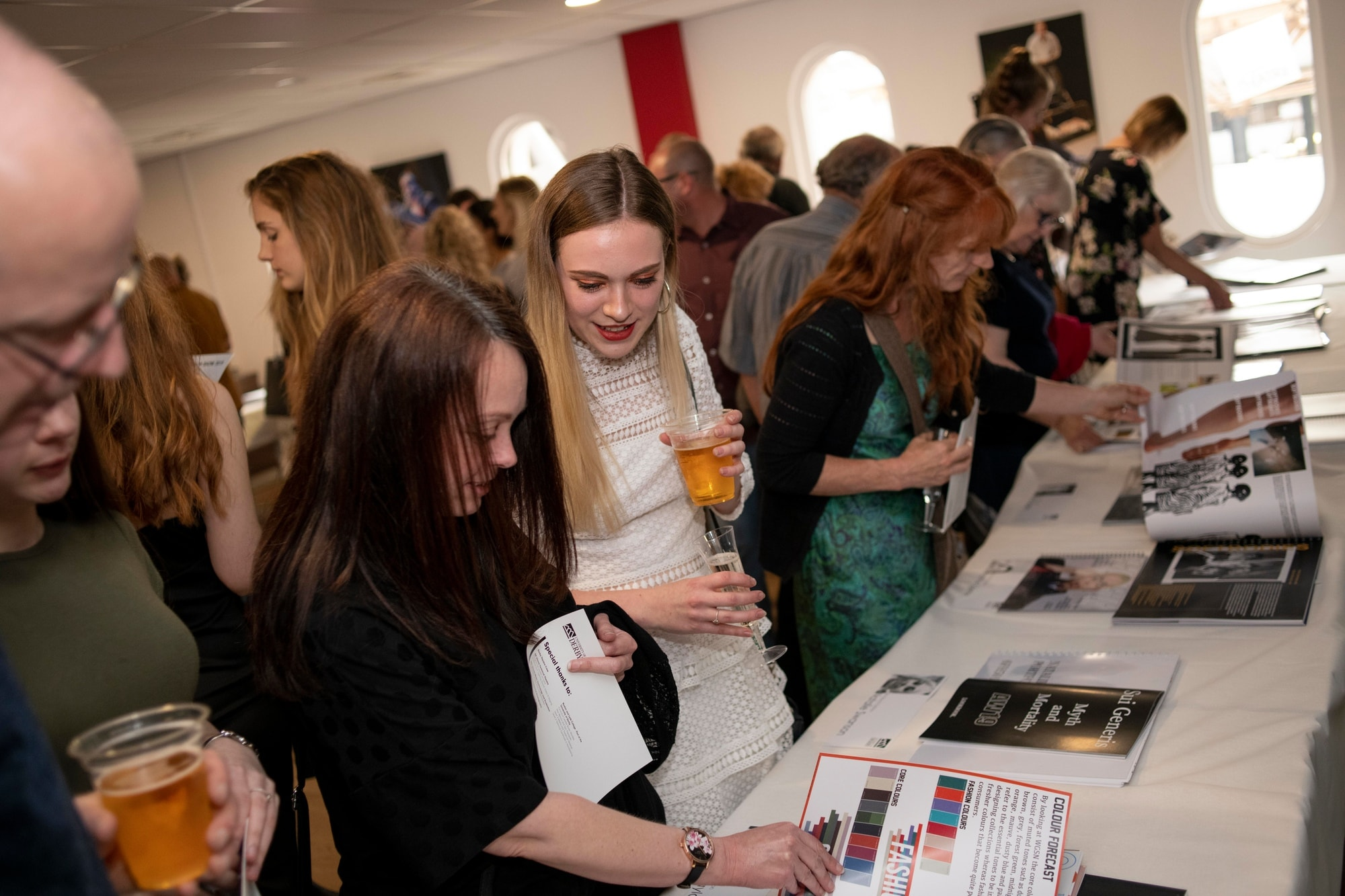 Visitors to the fashion show hold their drinks while leafing through student portfolios of final collections