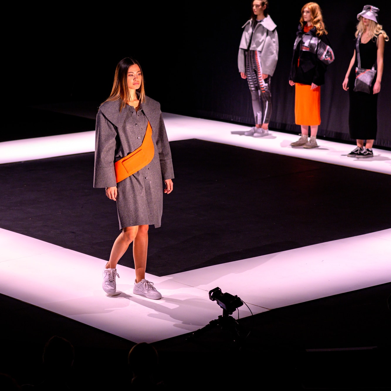A group of models on a catwalk wearing black, grey and orange designs