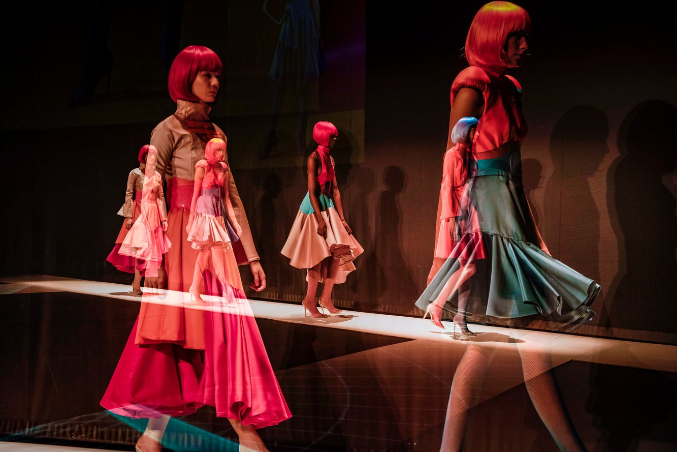 Female models in bright wigs walk the catwalk in bright and neon space themed dresses