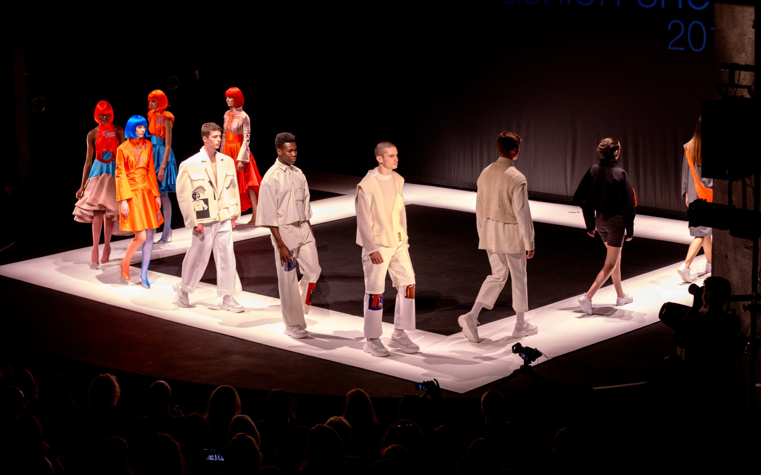 Models walk along a catwalk to showcase student collections