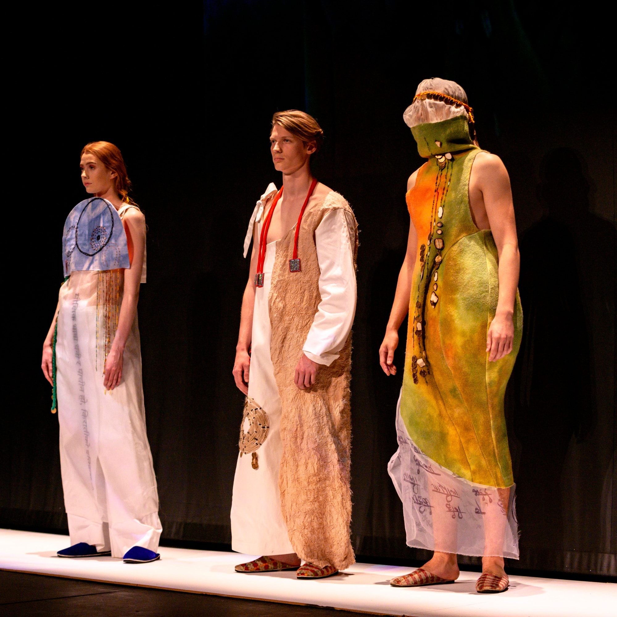 Image of 3 models on a catwalk showcasing a student's collection at the fashion show
