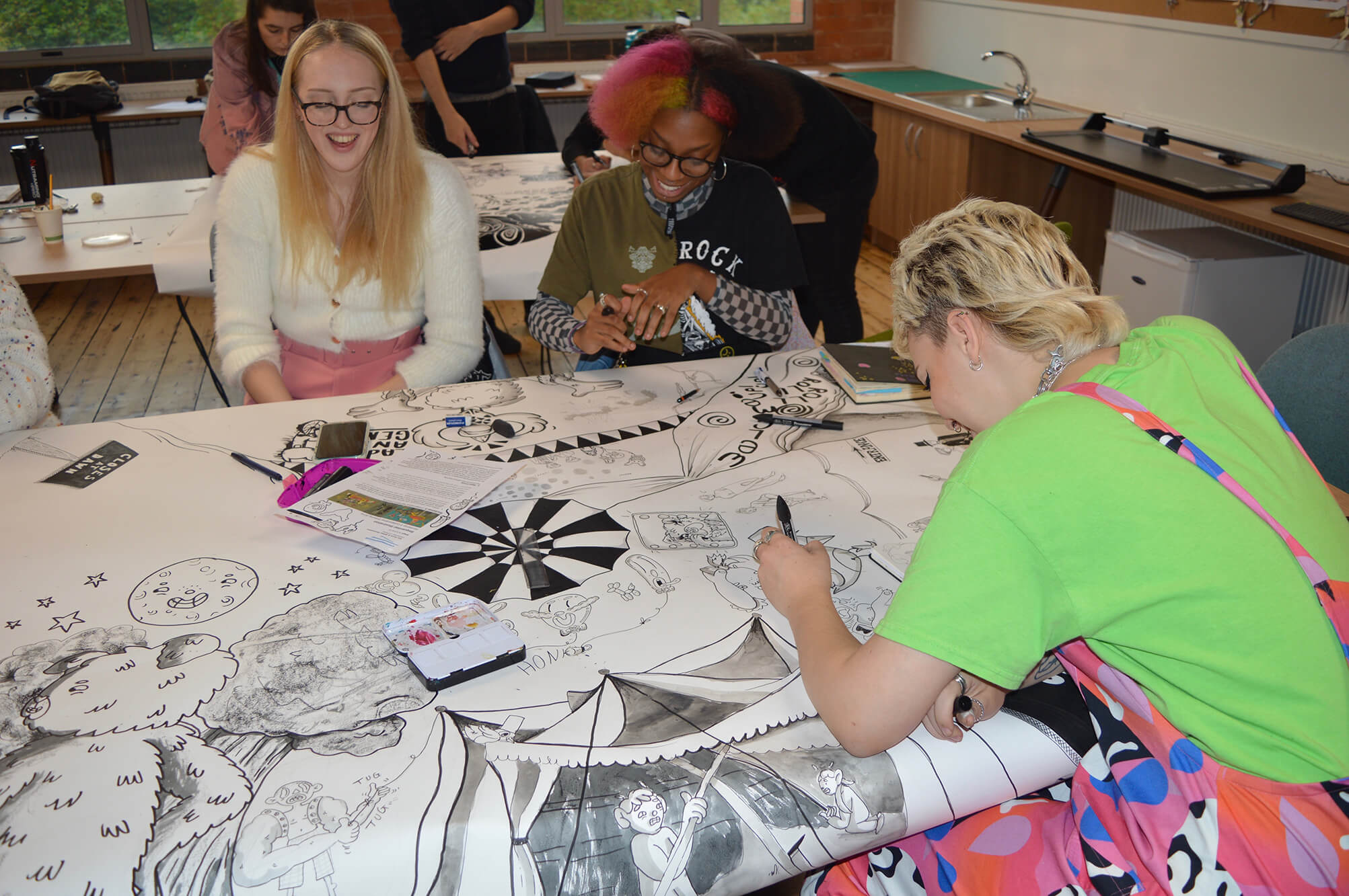 A group of illustration students work on a large black and white drawing