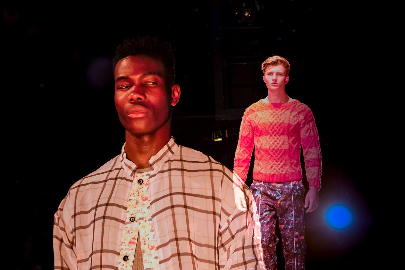 A male model in a cream checked shirt and another in a striped knitted pastel jumper