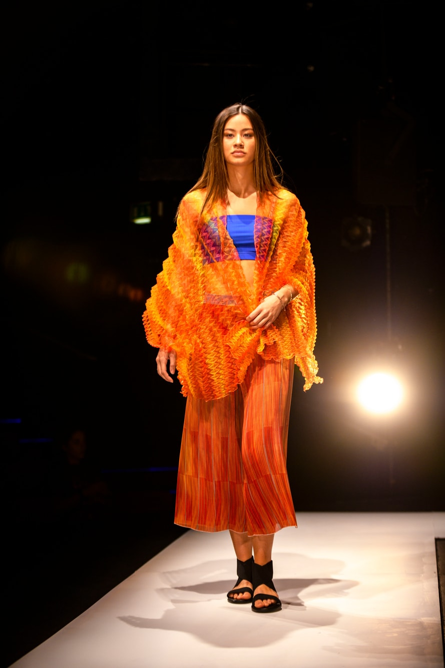A female model in a bright orange, ribbed, sea through flowing two piece with a blue bandeau underneath