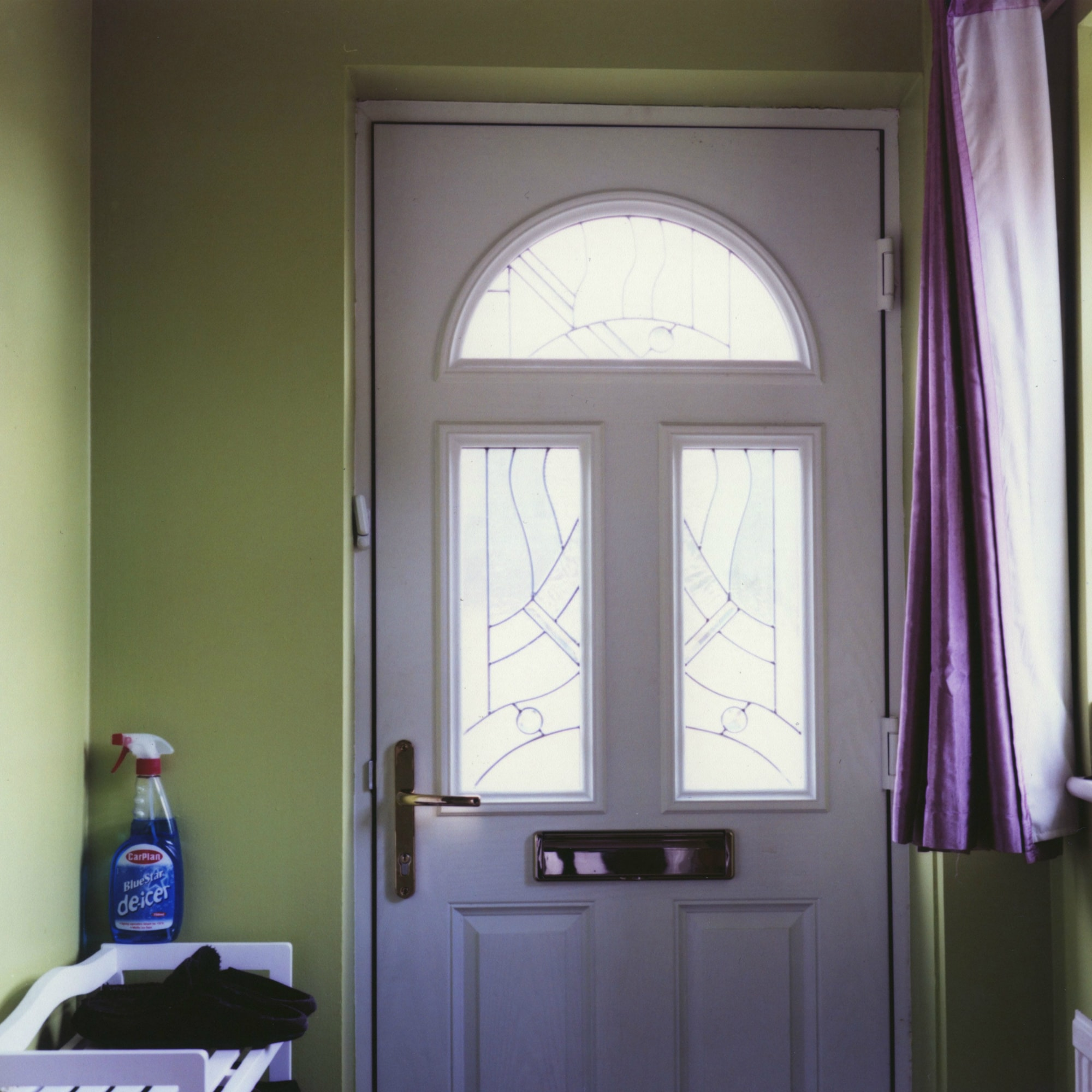 A photo of a front door of a house from the inside with purple curtains and household items nearby