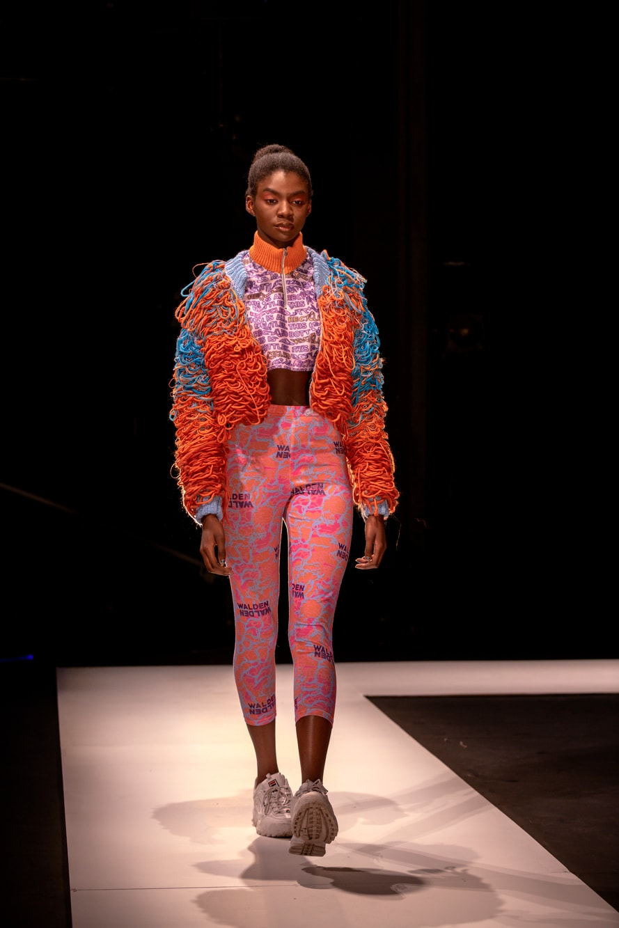 A female model in an oversized knitted brightly coloured jacket and bright sports trousers