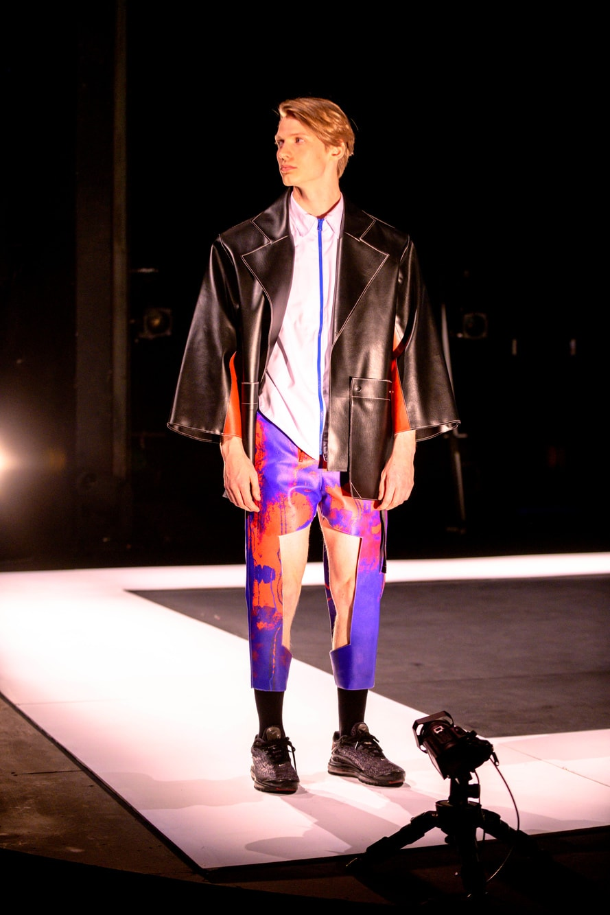 A male model turns to his right wearing an oversized leather look jacket and distressed bright trousers